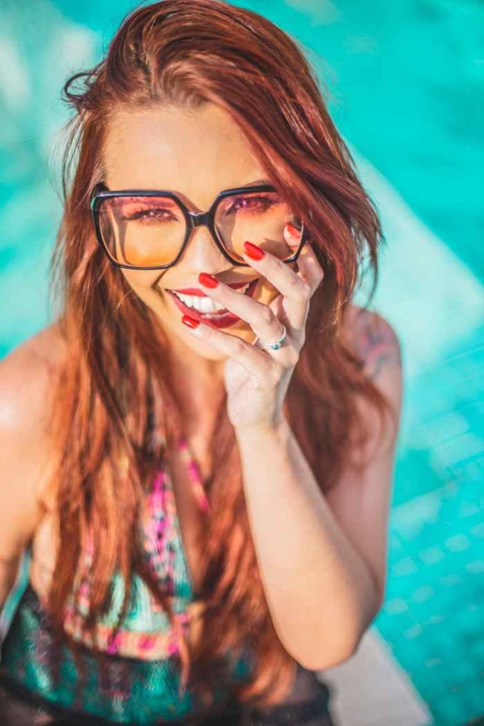 smiling woman wearing black frame eyeglasses